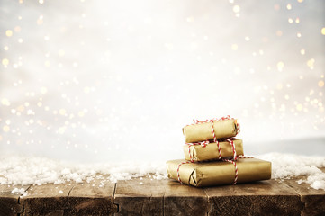 image of handmade wrapped gift boxes over wooden table covered with snow and silver glitter bokeh background.