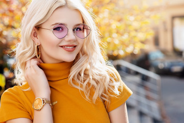 Happy smiling girl wearing purple sunglasses, yellow turtleneck, golden wrist watch, hoop earrings posing in street. Autumn fashion, advertising concept. Copy, empty space for text