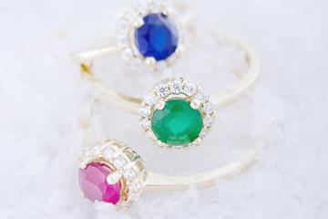 Collection of golden rings with colorful gems on snow background. Gemstones collection jewelry