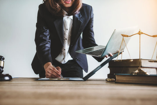 Lawyer or business woman using laptop with contact papers on table in office. wooden gavel justice and law ,attorney, court judge, concept.