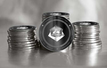 Etheera (ETA) digital crypto currency. Stack of black and silver coins. Cyber money.