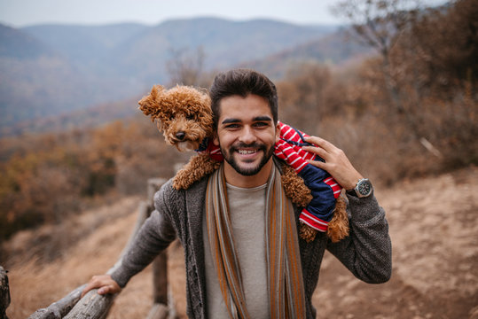 Man standing and holding dog on shoulders in nature.