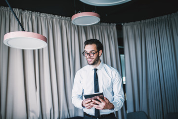 Close up of businessman using tablet while standing in lobby.
