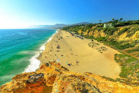 Aerial view of panoramic Point Dume State Beach from Point Dume promontory on Malibu coast, Pacific Ocean in CA, United States. California West Coast. Blue sky, summer season in sunny day. Copy space.