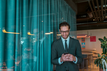 Smiling businessman standing in front of conference room and using smart phone.
