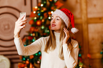 34b8f6aa212b4 beautiful smiling woman looking at smartphone and taking pictures. Christmas
