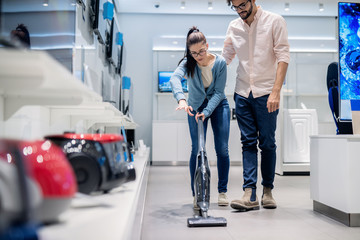 Woman trying out vacuum cleaner in tech store. New technologies concept.