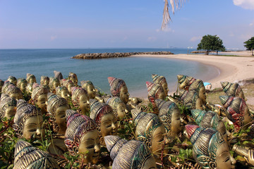 A collection of statues at a shrine overlooking a tropical beach and ocean in Thailand