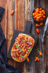 Bruschetta with prosciutto, tomato and basil on wooden board rustic style, copy space.
