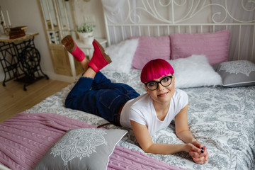 fashionable girl with pink hair lies on the bed