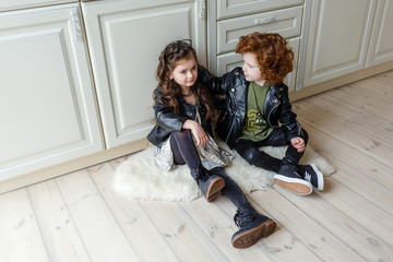 trend boy and girl are sitting on the floor in black leather clothes