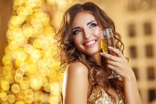 Portrait a beautiful glamour woman with champagne, holiday glowing background
