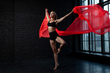 Young blonde ballerina in sportswear underwear dances and jumps in a studio with black brick on the background. modern ballet performance. Perfect fitness woman body