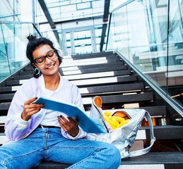 young cute indian girl at university building sitting on stairs
