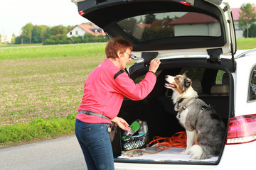 Mature woman with her dog in the rear of the car
