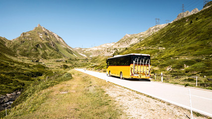 Public transportation in the mountains of switzerland named Postauto. Yellow bus on the road.