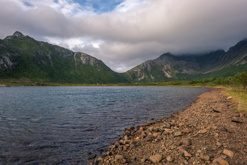 Rocky shore with green mountain peaks