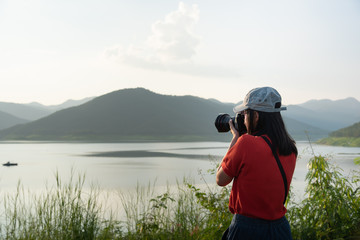 tourism woman hold camera for take a photo mountain and lake in journey trip