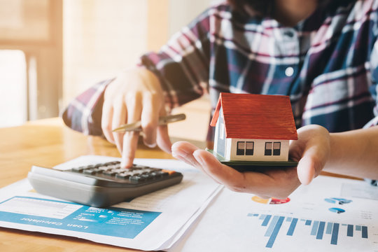 woman calculating budget before signing real estate project contract with house model at the table in the home