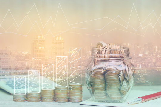 Double exposure of Graph on stack of coins money and the glass bottle on city background, investment and business concept