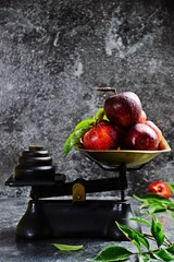 Red apples on the vintage style scale isolated on dark background