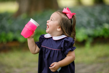 Little Toddler Preschool Girl in Navy Dress Drinking from Sippy Cup