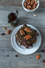 Caramel drizzled brownies with pecans on white plate