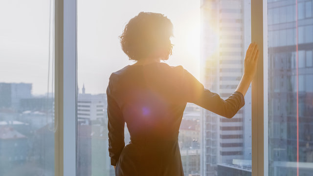 Shot of the Successful Businesswoman in a Striking Black Dress in Her Office Looking out of the Window at Sunset. Modern Business Office with Personal Computer and Big City View.