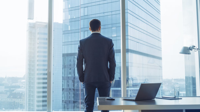 Back View of the Thoughtful Businessman wearing a Suit Standing in His Office, Hands in Pockets and Contemplating Next Big Business Deal, Looking out of the Window. Big City Panoramic Window View.