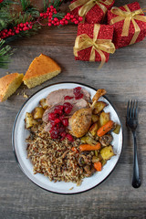 Christmas plated dinner with duck, cranberries, wild rice, cornbread, and roasted vegetables flat lay