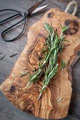 Fresh rosemary herb stalks on wood cutting board