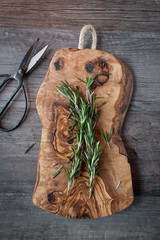 Fresh rosemary herb stalks on wood cutting board