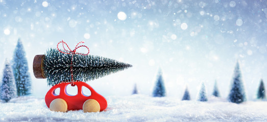 Red Car Carrying A Christmas Tree In Snowy Forest