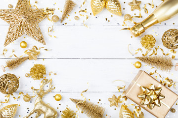 Christmas background with golden gift or present box, champagne and holiday decorations on white table top view. Greeting card. Flat lay style.