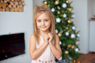 Happy little girl in luxury dress holds hands near face.With colorful lights and Christmas tree on background. Holidays, christmas, new year, x-mas concep