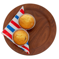 Homemade fruit muffins, cupcakes on red white and blue serviette, napkin on plate, isolated on white. Two small home baked cakes, overhead flat lay.