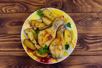Baked chicken drumsticks with potatoes in a plate on wooden table