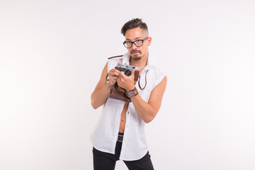 Technologies, photographing and people concept - handsome young man with retro camera over white background