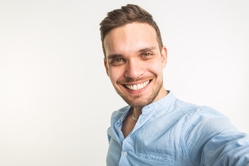 Fashion and people concept - handsome man make a selfie photo and smiling on white background