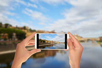 A tourist is taking a photo of quay of the Arno River and Ponte Vecchio Bridge in Florence, Italy on a mobile phone