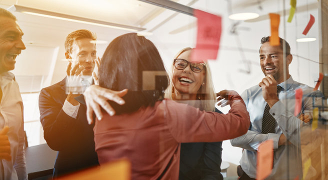 Businesswomen hugging while brainstorming with their team in an