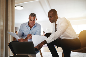 Two diverse businessmen discussing work together in an office