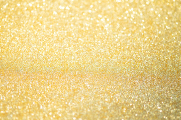 Abstract gold glitter bokeh lights with soft light background.
