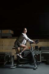 Fashion model in sports suit riding stationary fitness bike in storehouse during the brake between the show