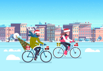 couple riding bike with fir tree gift box over city street buildings cityscape background merry christmas new year concept flat horizontal vector illustration