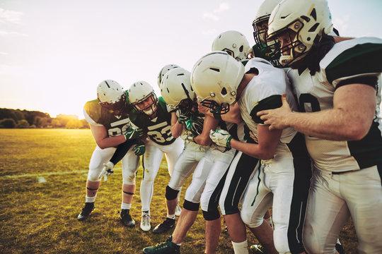American football team having fun with their captain during prac