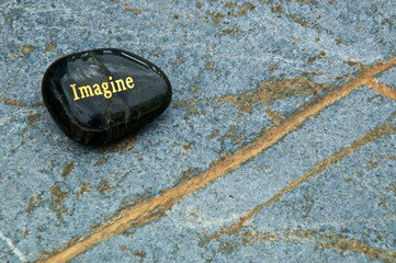 "A black polished stone with the word ""Imagine"" written in gold on a blue soapstone background, with copy space. Inspirational concept."