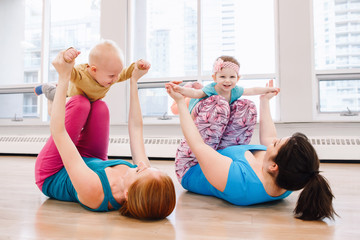 Group of two young women with children doing workout in gym class to loose baby weight....