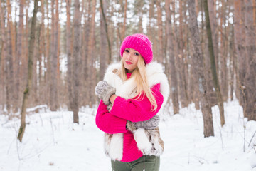 Fashion and people concept - Lovely young woman in warm jacket in winter park
