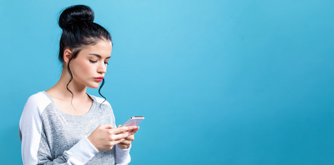 Young woman using her cellphone on a blue background